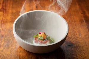 Ihr Vorgeschmack auf das Restaurant KITCHEN LIBRARY: Würziger Dry Aged Tatar mit Onsen-Ei, Rauch und marinierten Rosenblüten.